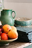 Bowl of apples next to folded dark grey cloths and ceramic pots