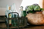 Glass bottles in metal bottle carrier next to ceramic vase of hydrangea flowers