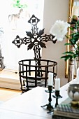 Delicate wrought iron cross in metal basket
