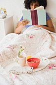 Frühstückstablett auf weisser Bettdecke; im Bett eine lesende, junge Frau