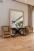 Side table with curved wooden frame in front of large free-standing mirror flanked by rattan armchairs on rustic wooden floor