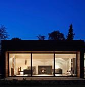 Nachtstimmung über zeitgenössischem Wohnhaus mit beleuchtetem Wohnzimmer