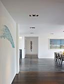 Grosszügiger, minimalistischer Wohnraum mit teilweise sichtbarem Essplatz in zeitgenössischem Wohnhaus
