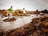 Bruder und Schwester spielen auf felsigem Strand