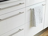 White kitchen base cabinets with stainless steel strip handles and polka-dot tea towel hanging over one handle