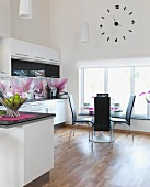 White, open-plan kitchen with magnolia-patterned splashbacks and dining area next to window below wall clock