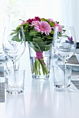 Bouquet of pink flowers, wine glasses and water glasses on festively set table