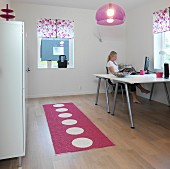 Home office with two desks and filing cabinet in plain white combined with polka-dot runner, plexiglass lampshade and floral blinds in pink