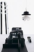 Black containers in felt trays on table, lamp sculpture and coat stand in background