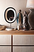 Ethnic figurine of woman with snake and Madonna between table lamp and oval mirror on cabinet