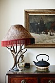 Antlers arranged around table lamp and Oriental teapot on antique cabinet; Buddha figurine and oil painting in background