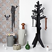 Coat stand and objets d'art on plinths against strip of floral wallpaper