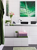 White-tiled bathroom with towels on step leading to whirlpool tub below picture with leaf motif