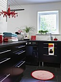 Modern laundry room with black base units, stainless steel strip handles, round rug and black tiled floor