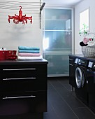 Modern laundry room with black base units, integrated washing machine and cupboard with glass sliding door in background