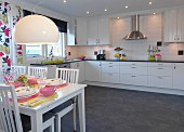 White chairs at set table in front of fitted kitchen with white cabinet fronts