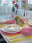 Place settings with heart-shaped plates and pink bowls on festive table