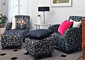 Armchairs and matching ottomans with ornate black pattern on grey upholstery in lounge area