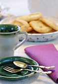 Vintage cutlery on green ceramic plates with dish of pastries in background