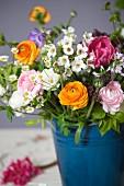 Frühlingsstrauss aus Ranunkeln, Tulpen, Apfelblüten in blauem Metallbehälter