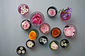 Spring flowers in colourful, vintage glasses decorating table