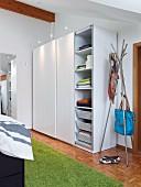Stauraumlösung im Schlafzimmer durch schlichten Schrank mit Schiebetüren und aufgesteckten Spotlights, daneben ein Garderobenständer