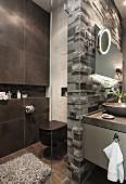WC neben dunkler Fliesenwand mit Ablagenische und Glasabtrennung; Kalksteinrelief als Waschtisch-Rückwand