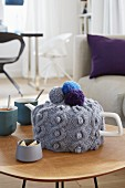 A knitted grey tea cosy decorated with colourful pompoms