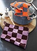 Knitted pot holders with colourful chess board patterns