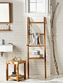 Teak stool next to ladder-style towel rack and gnarled branch against white-tiled wall in bathroom