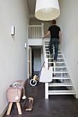 Mann auf weiss lackierter Holztreppe in schmalem Treppenraum mit dunkelgrauem Fliesenboden