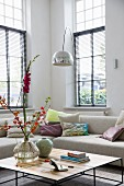 Coffee table, beige designer sofa and arc lamp in high-ceilinged living room with tall lattice windows