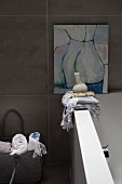 Towels on edge of bathtub below modern artwork on tiled wall