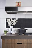 China vases and cast iron pan on kitchen counter in front of white and black wall tiles