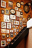 Collection of framed souvenir photos arranged on floral wallpaper alongside steep wooden staircase