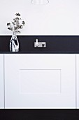 Vase of flowers on dark worksurface in designer kitchen with modern, angular, wall-mounted tap fitting