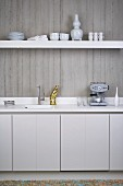 Kitchen counter and floating shelf on exposed concrete wall in minimalist, white, designer kitchen