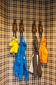Farbige Regenjacken, aufgehängt an Kleiderhaken in Form von menschenähnlichen Hasenfiguren vor braun kariertem Hintergrund