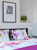 Double bed with floral bed linen and dark wooden headboard in modern bedroom