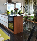 Walnut island counter in front of dining area with green chairs on glossy black-tiled floor and tree-patterned wallpaper