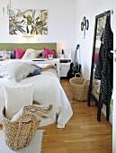 Doppelbett mit vielen Dekokissen und einem Tischgestell, geflochtene Körbe und Standspiegel in einem Schlafzimmer
