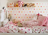 Love-heart pattern on bed linen and wallpaper in child's bedroom; collection of soft toys on wooden shelf and little blonde girl on metal bed