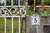 Rostiger, verwitterter Metallzaun & Mauer mit Hausnummer