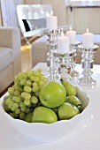 Green fruit in white china bowl in front of lit candles in candlesticks