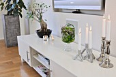 Lit, white candles in silver candlesticks on low, white sideboard in modern living room