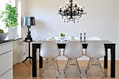 Classic chairs with white shell seats on metal frames around black dining table below chandelier in modern dining room