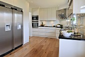 White designer kitchen with wooden floor and stainless steel fridge-freezer in niche