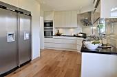 weiße Designerküche mit Dielenboden, seitlich Edelstahl Kühlschrankkombination in Nische