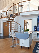 Scandinavian kitchen with island counter on castors in open-plan interior; steel and wood spiral staircase leading to upper storey