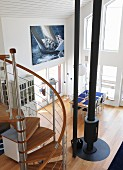 View from mezzanine down spiral staircase into double-height interior with central stovepipe and photo poster of sailing yacht